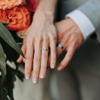 Two hands with wedding bands next to orange flowers